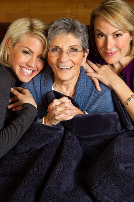 Family of three generation of women hugging and smiling.