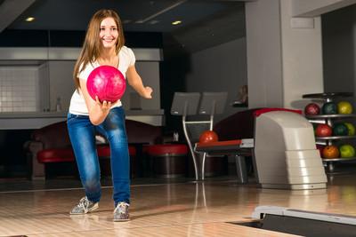 令人愉快的年轻女子投掷保龄球