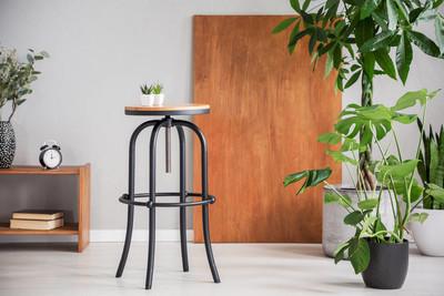 黑桌之间的木制橱柜和植物在灰色客厅内部与书桌。真实照片
