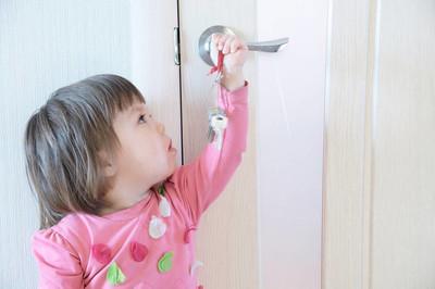 小孩在玩钥匙门钥匙孔的父母被遗忘了。儿童安全和家庭安全概念