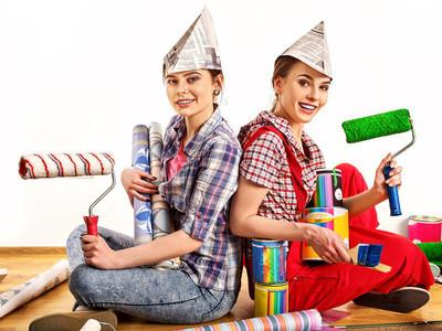 修理家里的女人抱着绘画工具辊的壁纸