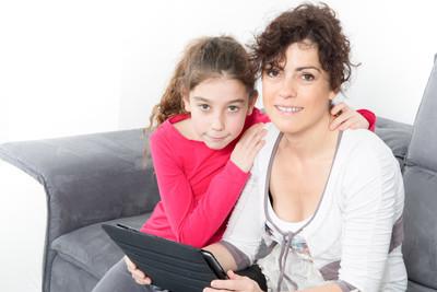 明亮的拥抱母亲和女儿看着平板电脑的图片