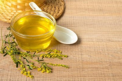 蜂蜜与野生花卉与黄色的三叶草,木制的桌子上的玻璃杯