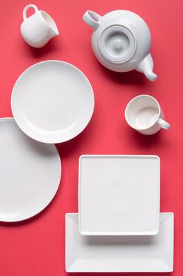 红色背景的白色陶器盘子和茶具