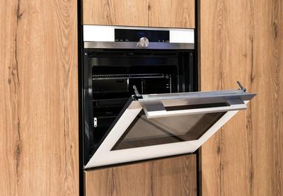 在木制的厨房橱柜里用烤箱建造, 门开着, 露出了近距离的空内部。