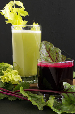 在黑色背景的玻璃杯中的蔬菜汁。甜菜, 芹菜, 胡萝卜
