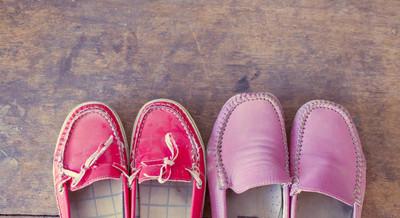 木材的背景上的粉红色和红色鞋