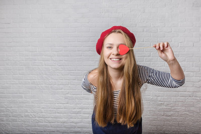 Funny young girl holding a red paper heart and laughing at the camera. Valentine's Day.