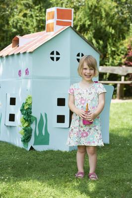 年轻女孩绘画纸板剧场在花园里