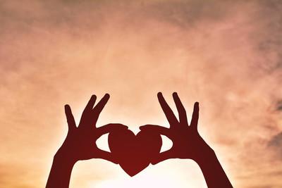 剪影手拿着心形状日落背景。概念的爱