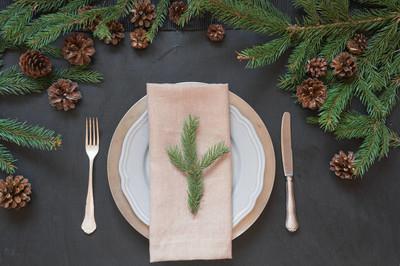 圣诞餐桌设置与银器和黑色桌子上的深天然常绿装饰。顶部视图。假日中心