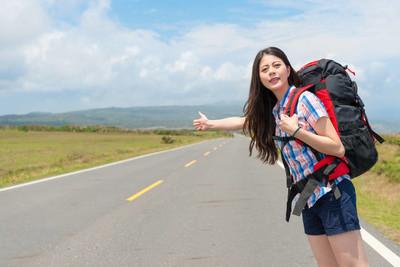 女人背着旅行背包站在公路上