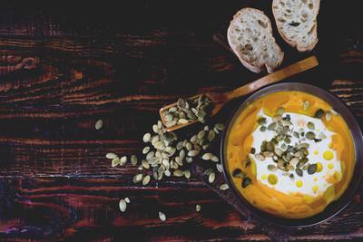 南瓜奶油汤与南瓜种子在木背景