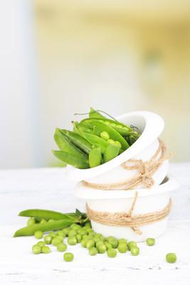 木制的桌子上的碗里的豌豆