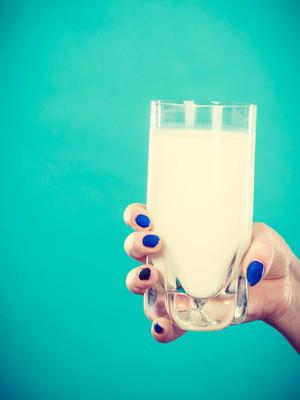 健康饮料、 良好的营养、 乳制品概念。女人手拿着杯牛奶