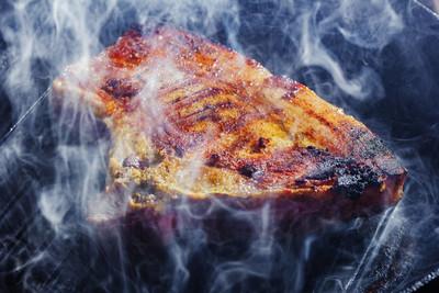 烟雾和蒸汽升起从猪肉牛排在烤盘上