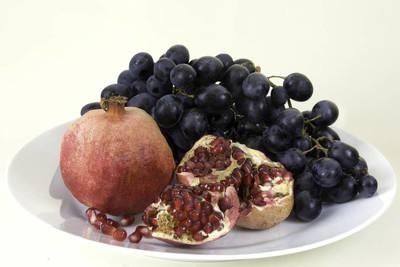 黑葡萄和红葡萄在白色的盘子上, 白色的背景