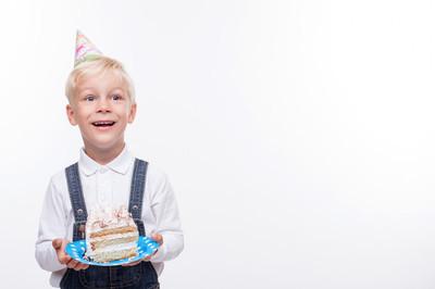 开朗的男性儿童在庆祝吃甜的食物