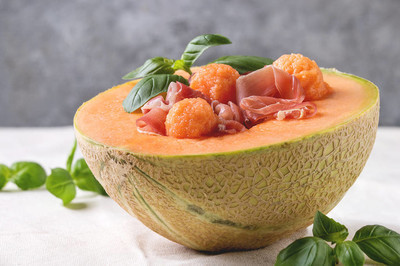 Melon and ham or prosciutto salad served in half of Cantaloupe melon, decorated by fresh basil standing on white tablecloth.