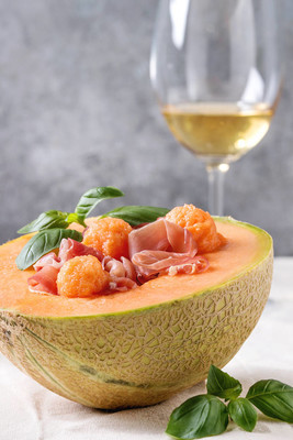 Melon and ham or prosciutto salad served in half of Cantaloupe melon, decorated by fresh basil standing on white tablecloth with glass of white wine. Close up