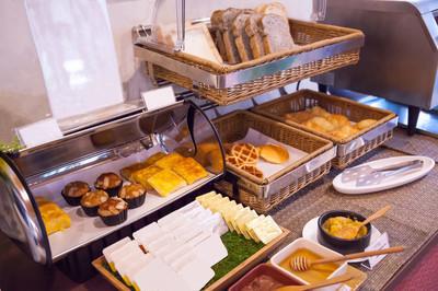 酒店餐厅餐饮服务健康早餐, 美式自助早餐套餐, 配有水果果酱、花生黄油、蜂蜜和人造黄油托盘的竹篮面包拼盘