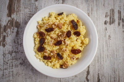 Cooked millet groats with raisins and walnuts on white plate, healthy food and nutrition