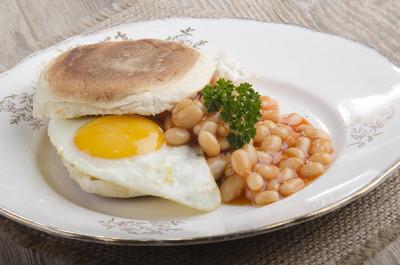 爱尔兰早餐与煎蛋和欧芹用烘烤的豆在板材