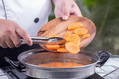 厨师把烹饪胡萝卜