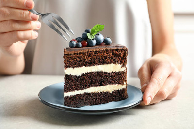 Woman with slice of chocolate sponge berry cake at table, closeup