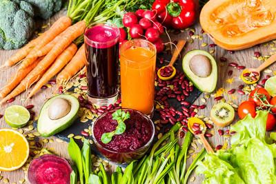 健康的素食食品。木制的背景上的新鲜蔬菜。排毒饮食。不同色彩的鲜榨果汁