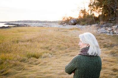 女人站在海岸附近的草地上