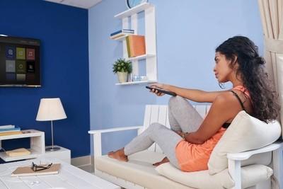 年轻的女人坐在沙发上,在家里看电视