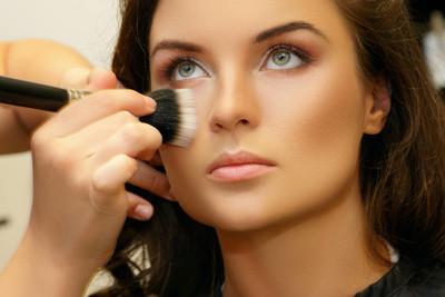 化妆师在模特脸上涂抹化妆品