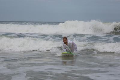英俊的新郎在夏天在海滩冲浪