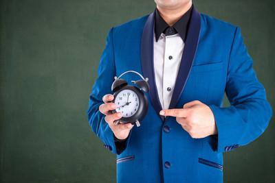 男子在西装持有和指向时钟板