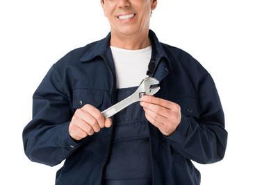愉快的水管工在均匀持有可调整的扳手在白色隔绝了
