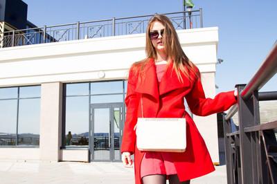 女商人,在办公大楼为背景的红色外套