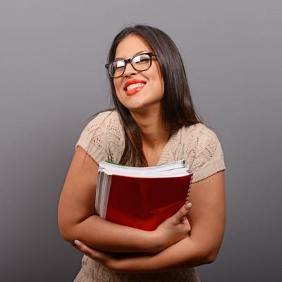 快乐的学生拿着书对灰色黑色的女人肖像