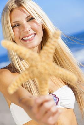 与海星在海滩比基尼美女女孩