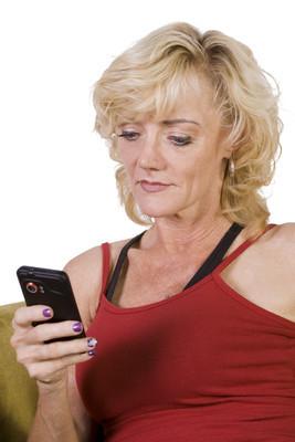 坐在沙发上的美丽的女人发短信
