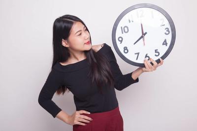 年轻的亚裔女子,和一个白色背景上的时钟