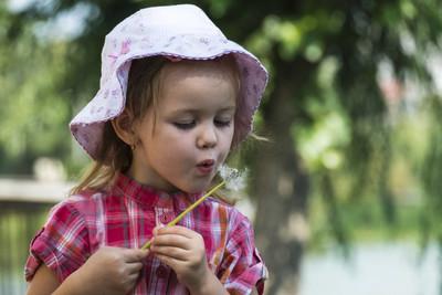 小女孩在帽子吹蒲公英