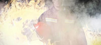 严肃的消防员反对灰色房间