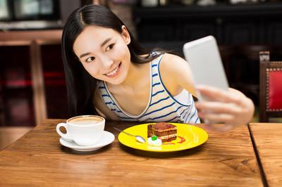 在咖啡馆店发短信在手机上的女孩