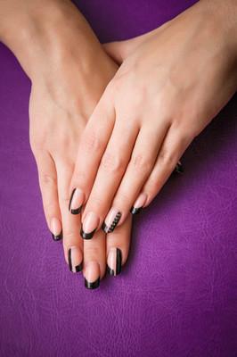紫罗兰色的背景上的黑色指甲的女性双手
