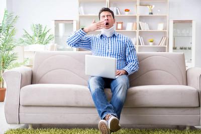 男人在颈托颈托在家工作的自由职业者