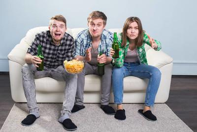 足球世界杯概念-年轻的朋友喝啤酒和欢呼足球