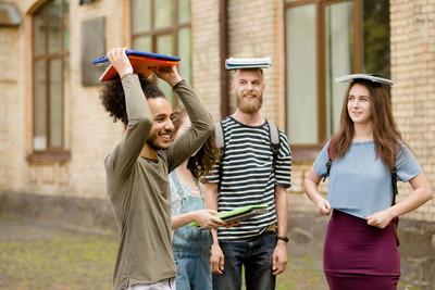 学生玩开心,拿着书在头上