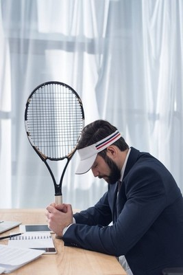 论职场中的忧郁商人与网球拍的侧面
