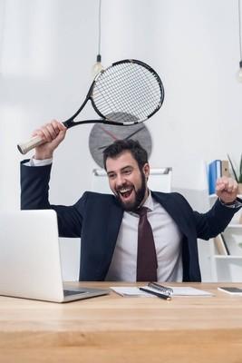 职场中与网球拍的兴奋商人肖像